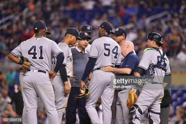 Teammates and trainers visit with Aroldis Chapman of the New York Yankees on the mound after Chapman was injured throwing a pitch in the twelfth...