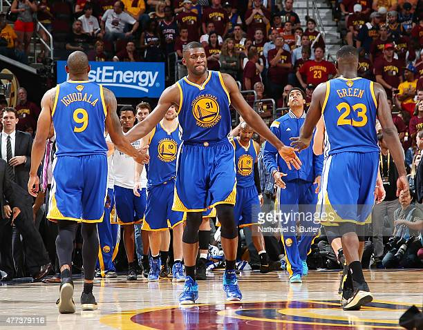 Teammates Andre Iguodala Festus Ezeli and Draymond Green of the Golden State Warriors highfive during Game Six of the 2015 NBA Finals at The Quicken...