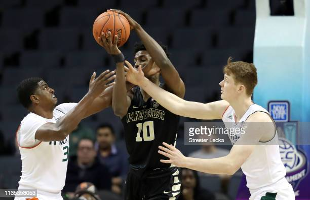 Teammates Anthony Lawrence II and Sam Waardenburg of the Miami Hurricanes battle for a loose ball against Jaylen Hoard of the Wake Forest Demon...