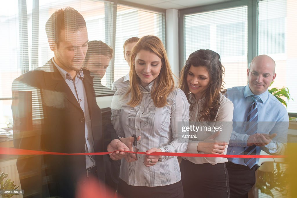 Teammates at an office cutting a ribbon for a new beginning : Stock Photo