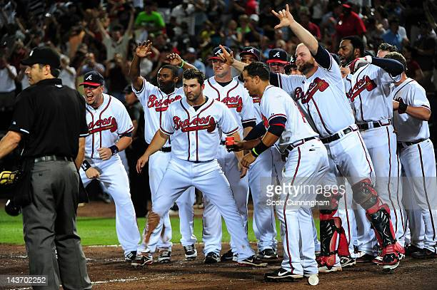 Teammates await Chipper Jones of the Atlanta Braves at home plate after hitting a 11th inning walk off home run against the Philadelphia Phillies at...