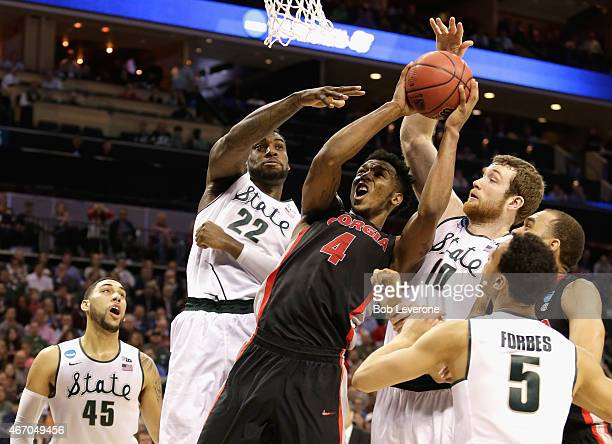 Teammates Branden Dawson and Matt Costello of the Michigan State Spartans try to stop Charles Mann of the Georgia Bulldogs during the second round of...