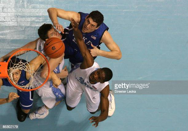 Teammates Brian Zoubek and teammate David McClure of the Duke Blue Devils battle for a rebound with teammates Bobby Frasor and Ed Davis of the North...