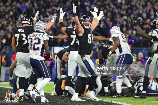 Teammates celebrate a touchdown by quarterback Lamar Jackson of the Baltimore Ravens against the New England Patriots during the fourth quarter at MT...
