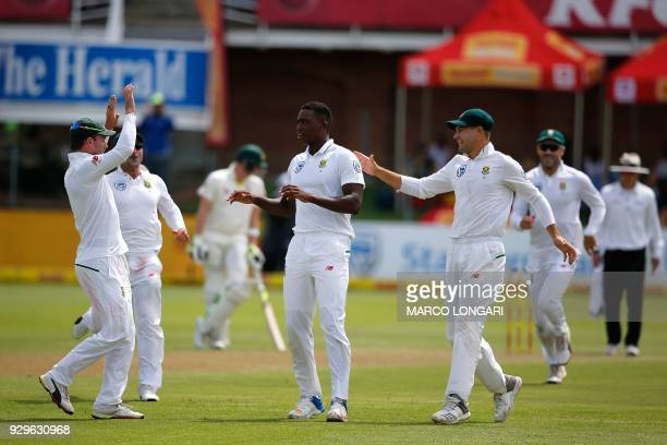 Teammates celebrate South Africa bowler Lungi Ngidi taking the wicket of Australia batsman David Warner during day one of the second Sunfoil Test...