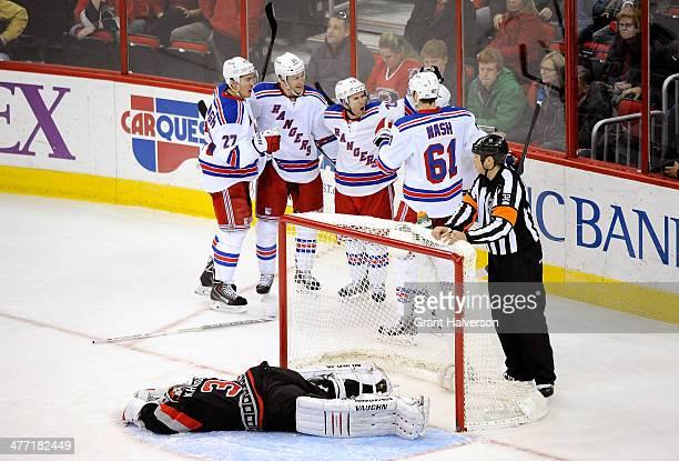Teammates celebrate with Derek Stepan of the New York Rangers after his game-winning goal against Anton Khudobin of the Carolina Hurricanes during...