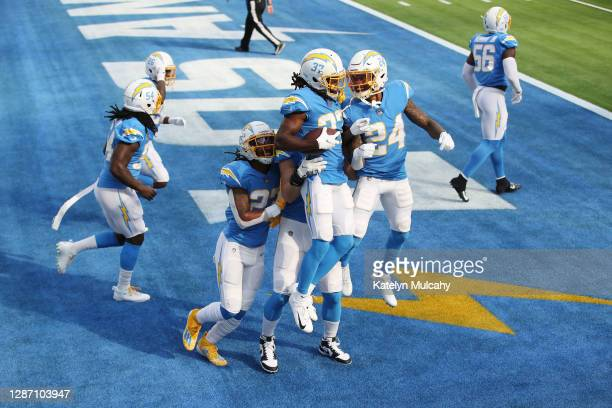 Teammates celebrate with Tevaughn Campbell of the Los Angeles Chargers after his pick six during the first half against the New York Jets at SoFi...