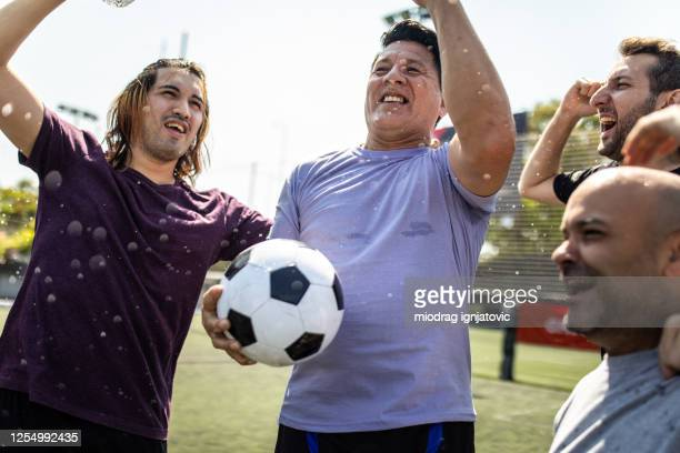 teammates celebrating winning a match at soccer field - friendly match stock pictures, royalty-free photos & images