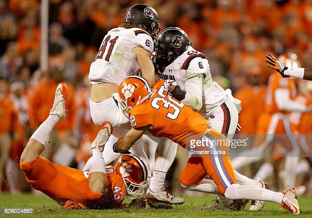 Teammates Chad Smith and Christian Wilkins of the Clemson Tigers stop Hayden Hurst of the South Carolina Gamecocks on a fake punt during their game...