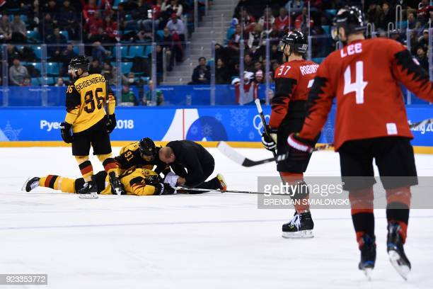 TOPSHOT Teammates check on Germany's David Wolf as he lies on the ice after being hit in the men's semifinal ice hockey match between Canada and...