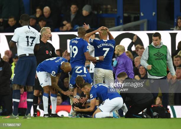 Teammates comfort Everton's Portuguese midfielder André Gomes as he gets attention for an injury during the English Premier League football match...