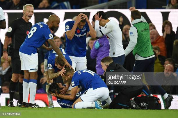 TOPSHOT Teammates comfort Everton's Portuguese midfielder André Gomes as he gets attention for an injury during the English Premier League football...