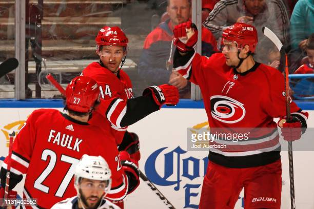 Teammates congratulate Justin Williams of the Carolina Hurricanes after he scored the game winning goal against the Florida Panthers at the BBT...