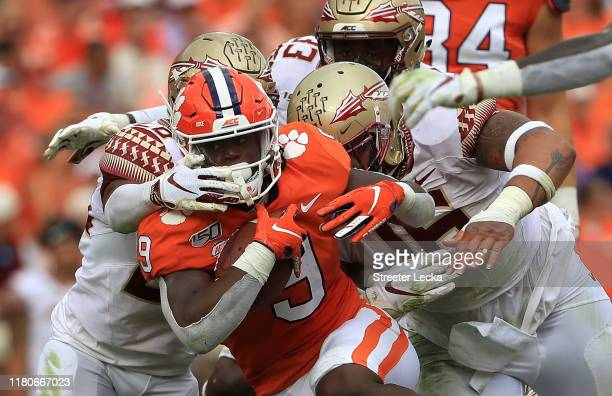 Teammates Cory Durden and Keyshawn Helton of the Florida State Seminoles try to stop Travis Etienne of the Clemson Tigers during their game at...