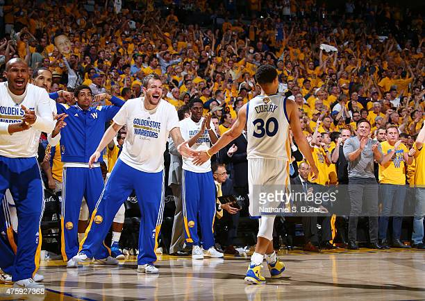 Teammates David Lee of the Golden State Warriors and Stephen Curry of the Golden State Warriors highfive during Game One of the 2015 NBA Finals on...