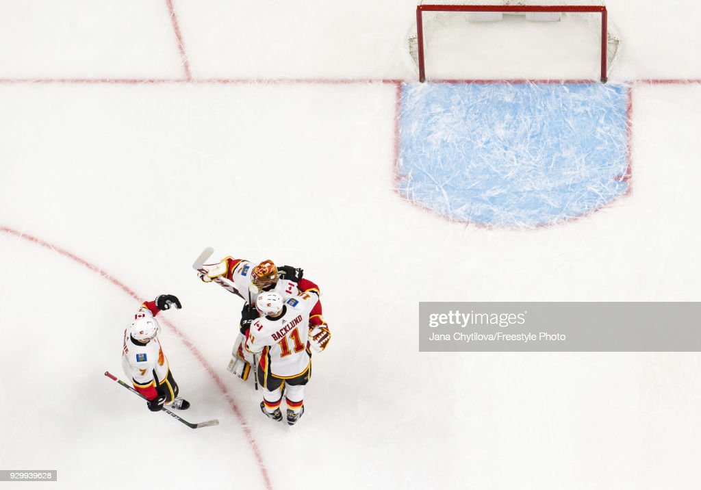 Teammates David Rittich #33, TJ Brodie #7 and Mikael Backlund #11 of the Calgary Flames celebrate their win against the Ottawa Senators at Canadian Tire Centre on March 9, 2018 in Ottawa, Ontario, Canada.
