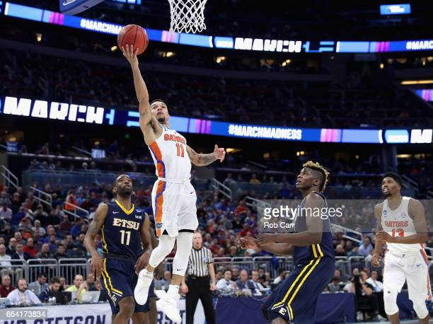 Teammates Desonta Bradford and Hanner MosqueraPerea of the East Tennessee State Buccaneers watch as Chris Chiozza of the Florida Gators drives to the...