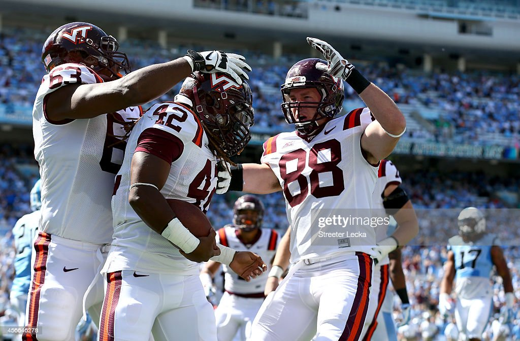 Teammates Drew Burns #53 and Ryan Malleck #88 celebrate with Marshawn Williams #42 of the Virginia Tech Hokies after he ran for a touchdown against the North Carolina Tar Heels during their game at Kenan Stadium on October 4, 2014 in Chapel Hill, North Carolina.
