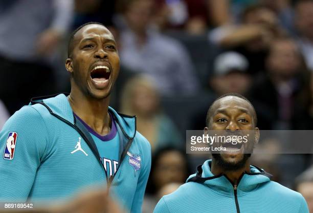 Teammates Dwight Howard and Kemba Walker of the Charlotte Hornets react on the bench during their game against the Milwaukee Bucks at Spectrum Center...