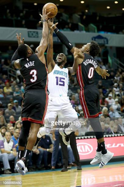 Teammates Dwyane Wade and Josh Richardson of the Miami Heat try to stop Kemba Walker of the Charlotte Hornets during their game at Spectrum Center on...