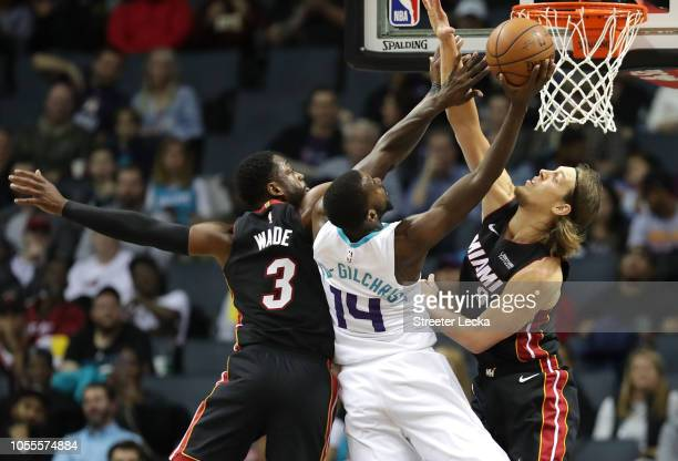 Teammates Dwyane Wade and Kelly Olynyk of the Miami Heat try to stop Michael KiddGilchrist of the Charlotte Hornets during their game at Spectrum...