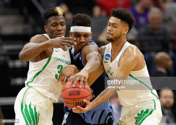Teammates Dylan Ennis and Tyler Dorsey of the Oregon Ducks go after a loose ball against EC Matthews of the Rhode Island Rams during the second round...