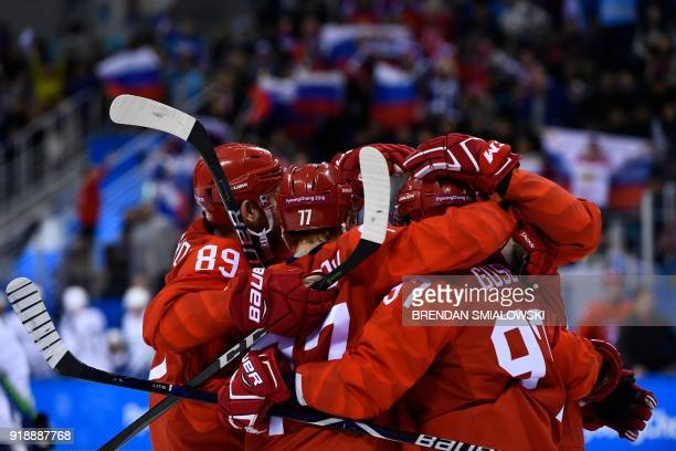 Teammates embrace Russia's Kirill Kaprizov after he scored in the men's preliminary round ice hockey match between the Olympic Athletes from Russia...