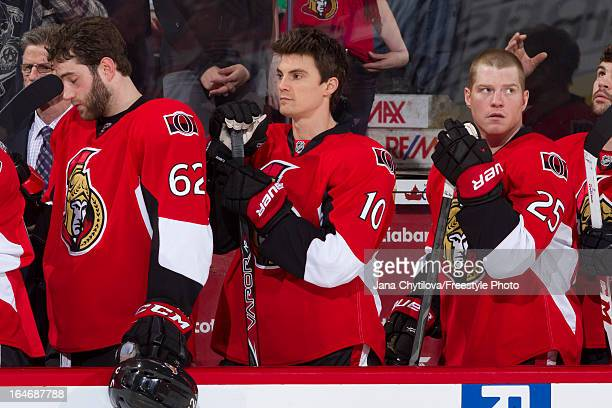 Teammates Eric Gryba Mike Lundin and Chris Neil of the Ottawa Senators look on during the singing of the national anthems prior to an NHL game...