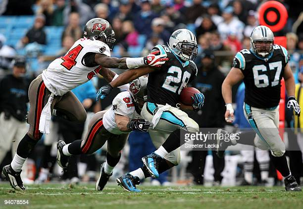 Teammates Geno Hayes and Barrett Ruud of the Tampa Bay Buccaneers tackle Jonathan Stewart of the Carolina Panthers during their game at Bank of...