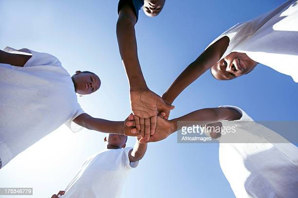 teammates hands together, gugulethu, cape town, south africa. - gugulethu stock pictures, royalty-free photos & images