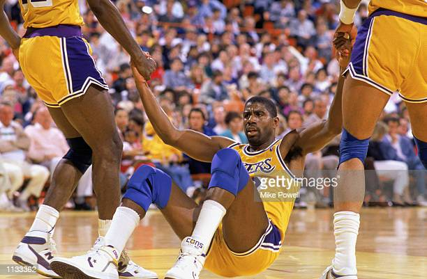 Teammates help Magic Johnson of the Los Angeles Lakers off the floor during an NBA game at the Great Western Forum in Los Angeles California in 1987
