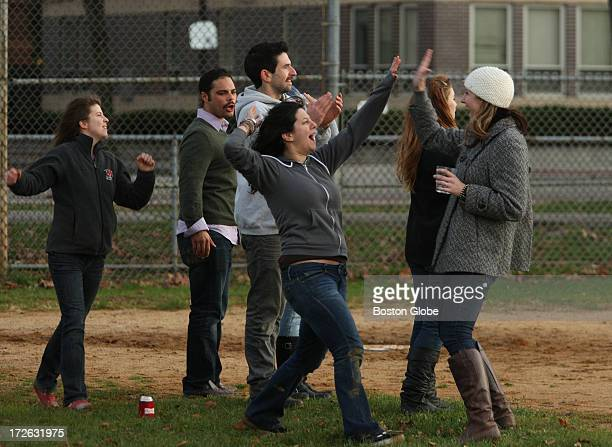 Teammates high five each other after one of the teams scored a run while they played kickball at a Northeastern University field near the...