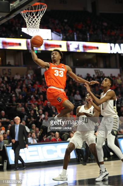 Teammates Isaiah Mucius and Jaylen Hoard of the Wake Forest Demon Deacons watch as Elijah Hughes of the Syracuse Orange drives to the basket during...