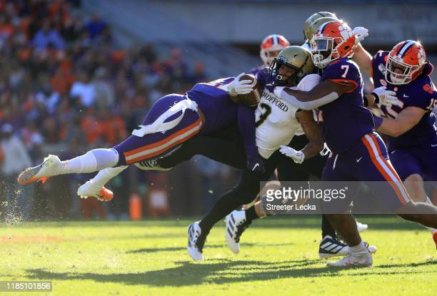 Teammates Isaiah Simmons and Justin Mascoll of the Clemson Tigers tackle D'mauriae VanCleave of the Wofford Terriers during their game at Memorial...