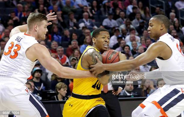 Teammates Jack Salt and Devon Hall of the Virginia Cavaliers try to stop Jairus Lyles of the UMBC Retrievers during the first round of the 2018 NCAA...