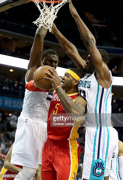 Teammates Jason Maxiell and Noah Vonleh of the Charlotte Hornets try to stop Josh Smith of the Houston Rockets during their game at Time Warner Cable...