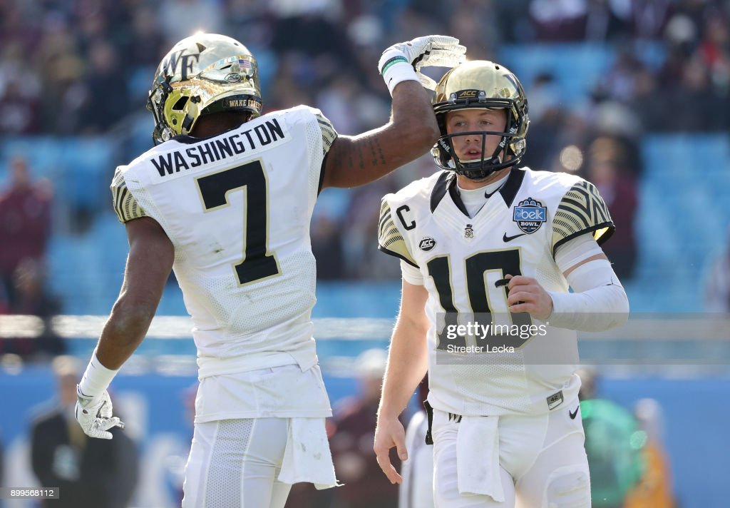 Teammates John Wolford #10 and Scotty Washington #7 of the Wake Forest Demon Deacons celebrate after a touchdown against the Texas A&M Aggies during the Belk Bowl at Bank of America Stadium on December 29, 2017 in Charlotte, North Carolina.