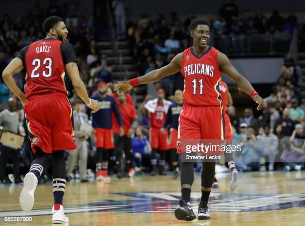 Teammates Jrue Holiday and Anthony Davis of the New Orleans Pelicans react after a play during their game against the Charlotte Hornets at Spectrum...