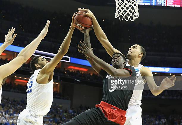 Teammates Karl-Anthony Towns and Trey Lyles of the Kentucky Wildcats block Shaquille Thomas of the Cincinnati Bearcats during the third round of the...