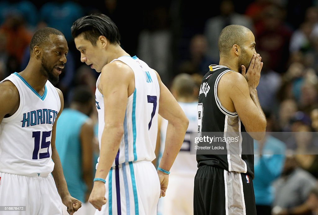 Teammates Kemba Walker #15 and Jeremy Lin #7 of the Charlotte Hornets celebrate as Tony Parker #9 of the San Antonio Spurs reacts during their game at Time Warner Cable Arena on March 21, 2016 in Charlotte, North Carolina.NOTE