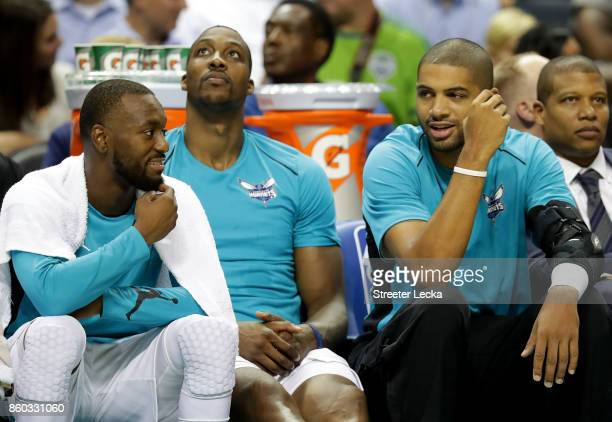 Teammates Kemba Walker Dwight Howard and Nicolas Batum of the Charlotte Hornets talk on the bench against the Boston Celtics during their game at...