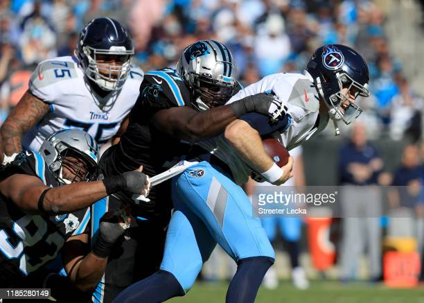 Teammates Kyle Love and Gerald McCoy of the Carolina Panthers try to stop Ryan Tannehill of the Tennessee Titans during their game at Bank of America...