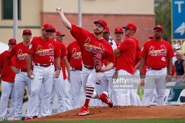 Teammates look on as Miles Mikolas of the St Louis Cardinals warms up in the bullpen prior to the spring training game against the New York Mets at...
