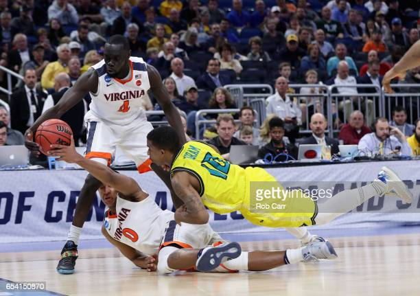 Teammates Marial Shayok and Devon Hall of the Virginia Cavaliers battle for a loose ball against Denzel Ingram of the North CarolinaWilmington...