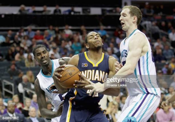 Teammates Marvin Williams and Cody Zeller of the Charlotte Hornets try to stop Glenn Robinson III of the Indiana Pacers during their game at Spectrum...