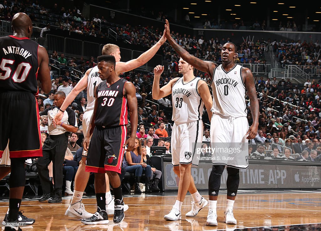 Teammates Mason Plumlee #1 and Andray Blatche #0 of the Brooklyn Nets high five during a preseason game against the Miami Heat at the Barclays Center on October 17, 2013 in the Brooklyn borough of New York City.