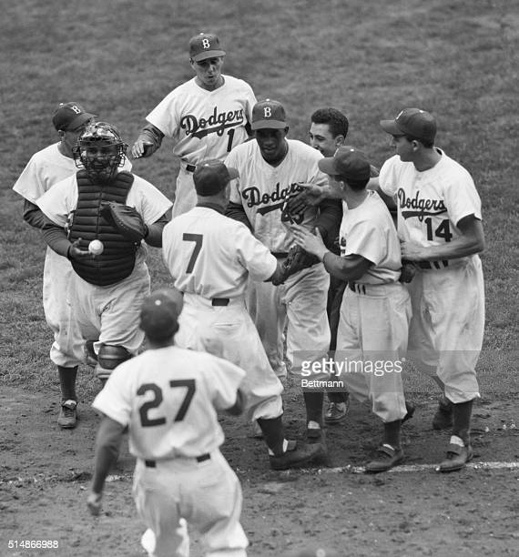 Teammates mob Brooklyn Dodgers' starting pitcher Joe Black after he led his team to a win over the New York Yankees in the opening game of the 1952...