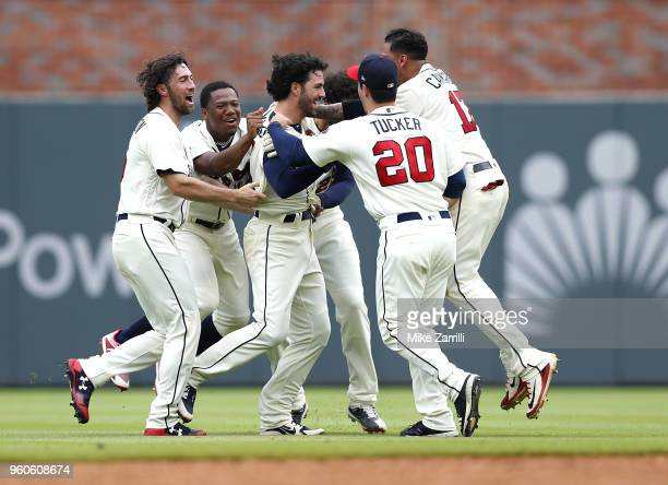 Teammates mob Dansby Swanson of the Atlanta Braves after he hit a tworun gamewinning walkoff single in the ninth inning during the game against the...