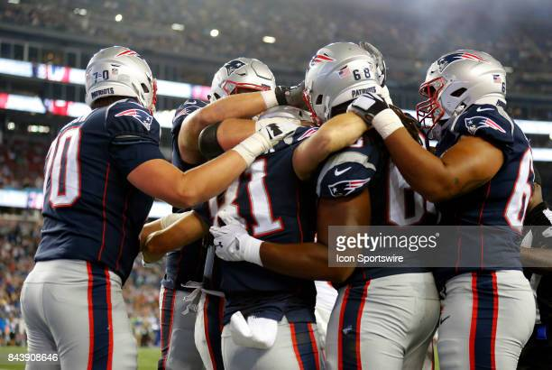 Teammates mob New England Patriots wide receiver Cody Hollister after his touchdown during an NFL preseason game between the New England Patriots and...