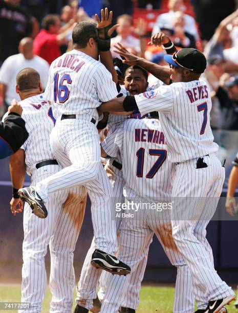 teammates mob Ruben Gotay of the New York Mets after he scored the winning run off of a Carlos Delgado hit off of pitcher Scott Eyre of the Chicago...